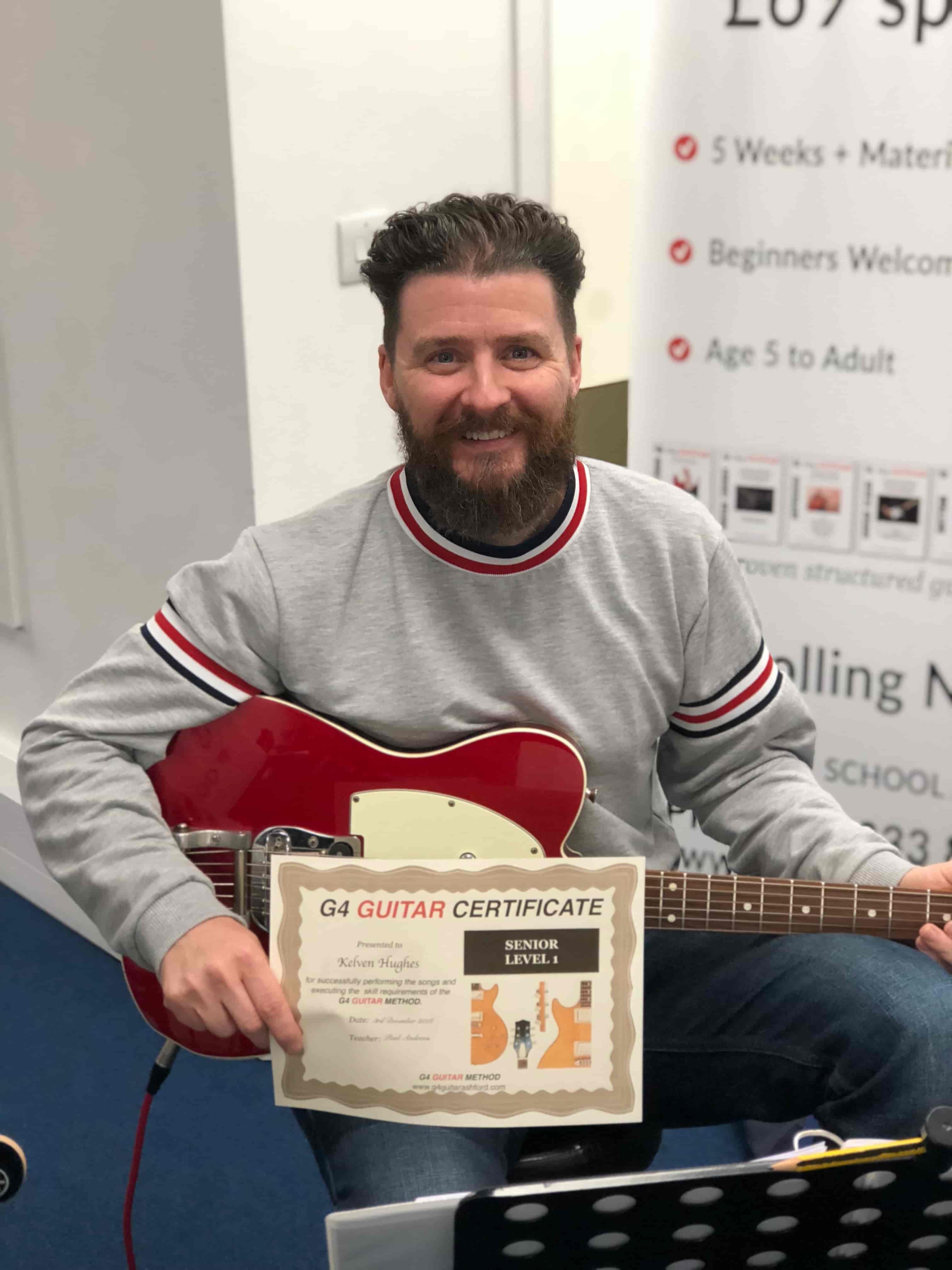 kelven-holding-guitar-certificate