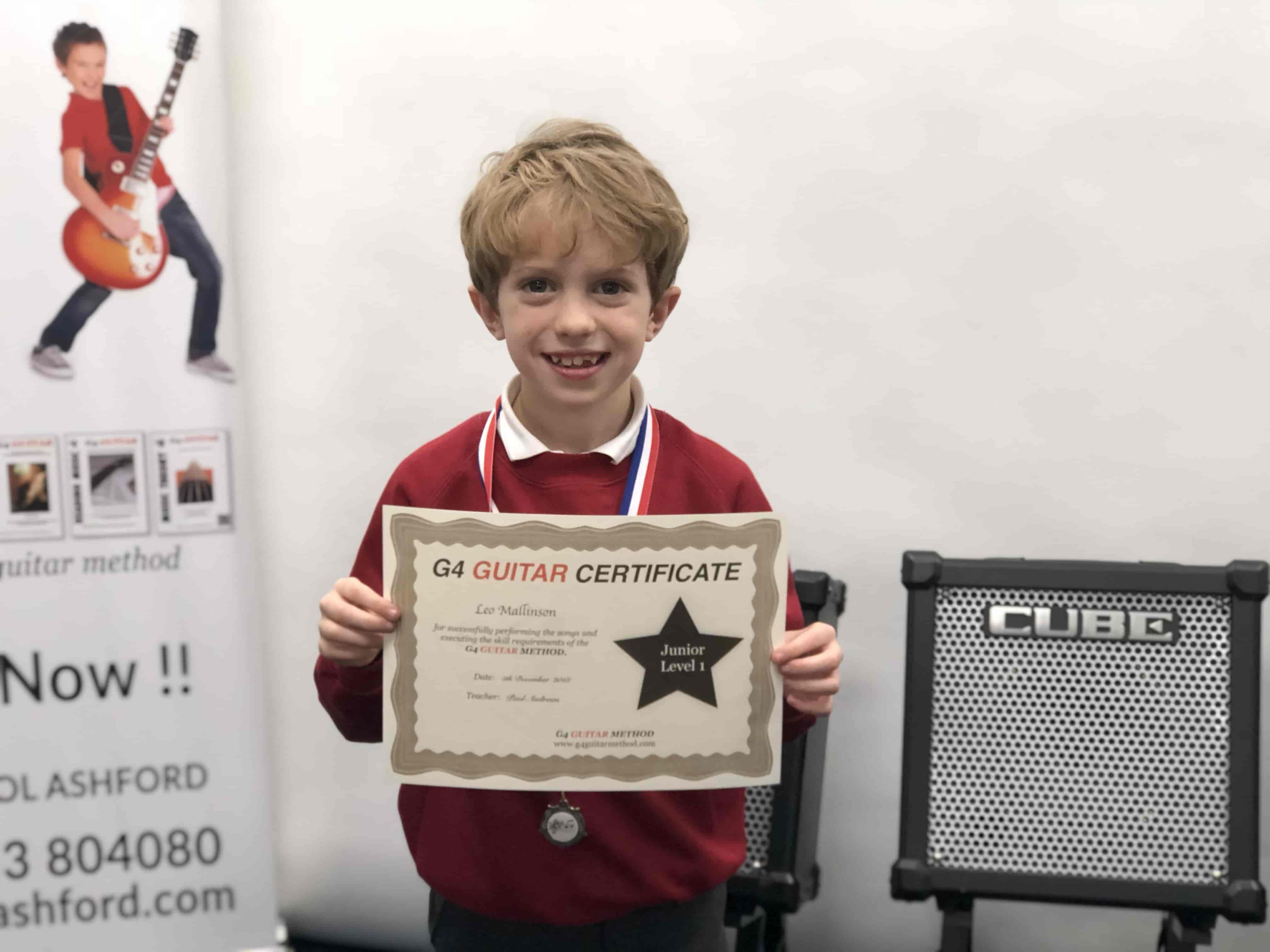 leo-holding-guitar-certificate