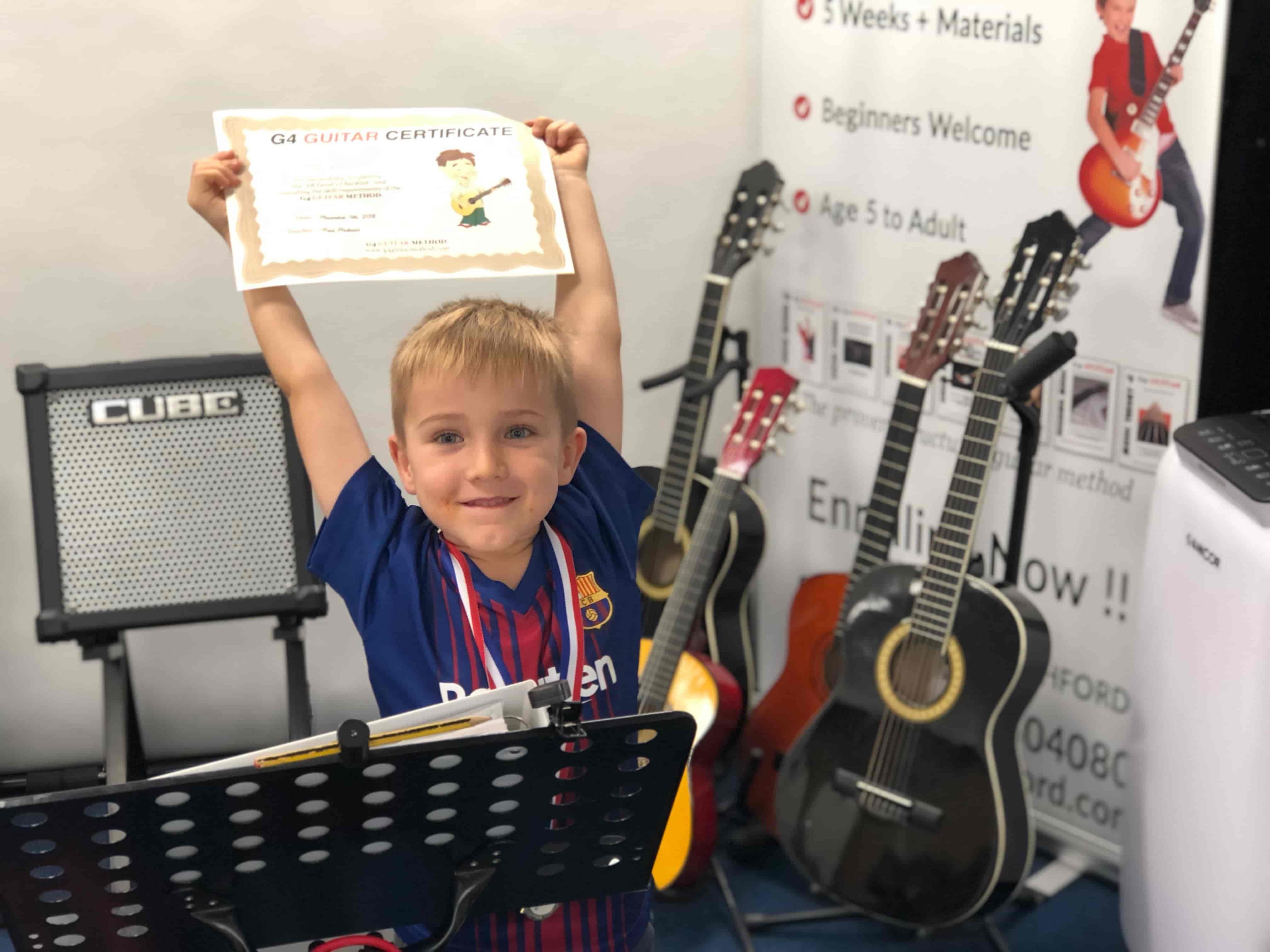 seth-holding-guitar-certificate
